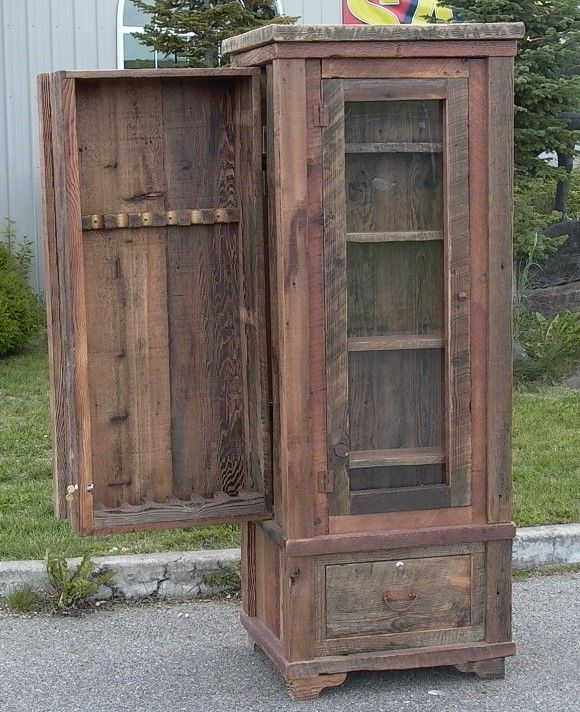 A custom barn wood cabinet with a glass door, drawer below ...