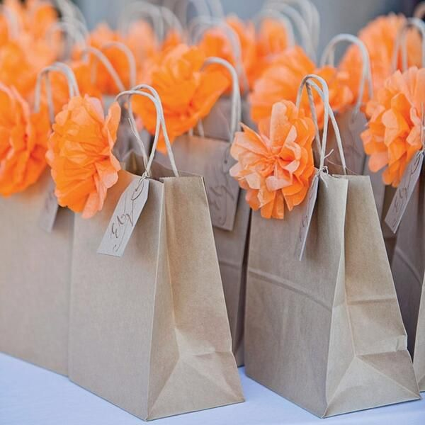 Simple brown paper sacks with cute flower poms for inexpensive wedding welcome bag.