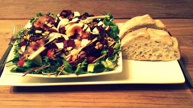 Gemengde salade met ei, tomaat, advocado, radijsjes, rode biet, maïs, spek, appel, zwarte olijven, feta, walnoten en balsamicocrème