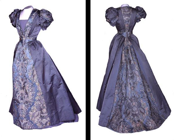 Women's Evening Dress Blue satin and 18th century brocade evening dress with belt. In the 1890s the bustle was disappearing and skirts were becoming narrower, often with trains. To shift attention from the skirt, sleeves were emphasised. Puff sleeves, like those on this dress, were very much in vogue and became more exaggerated. Artist / Maker: J. C. Webber, Maidenhead Place: England Object Type: evening dress Period: Victoria Broad Date: Late Victorian Actual Date: c. 1892 Century: 19th…