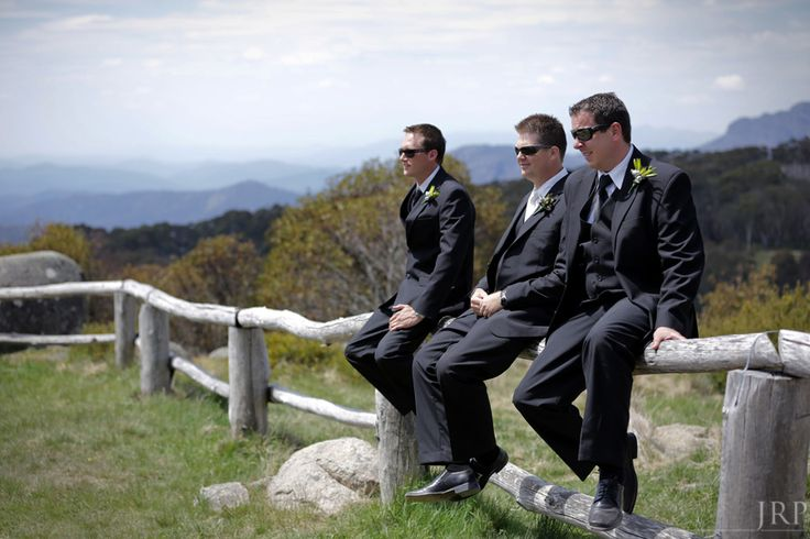 Groom and Groomsmen sitting on a fence at Craig's Hut