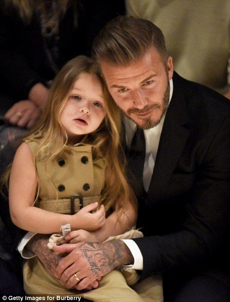 Cuddles: The dad-and-daughter duo kept close as they watched the show, while the three-year-old looked adorable in a miniature trench coat-style dress
