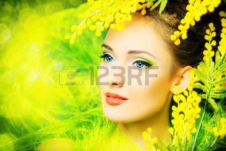Ritratto di una bella ragazza con fiori di mimosa. Primavera. photo