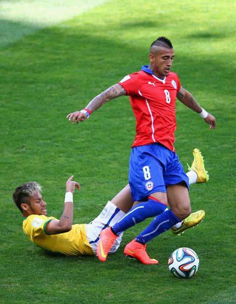 Neymar of Brazil challenges Arturo Vidal of Chile during the 2014 FIFA World Cup Brazil round of 16 match between Brazil and Chile at Estadio Mineirao on June 28, 2014 in Belo Horizonte, Brazil.