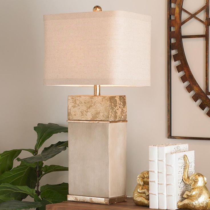 """Concrete Block Gold Leaf Table Lamp A concrete block takes on a transitional style when accented with antique gold and topped with a tan linen shade. Rustic to modern, this table lamp serves up an eclectic combination of style and elegance. 100 watt max medium base lamp. (32""""Hx16""""Wx9""""D) Shade (16""""x9""""x11""""H)."""