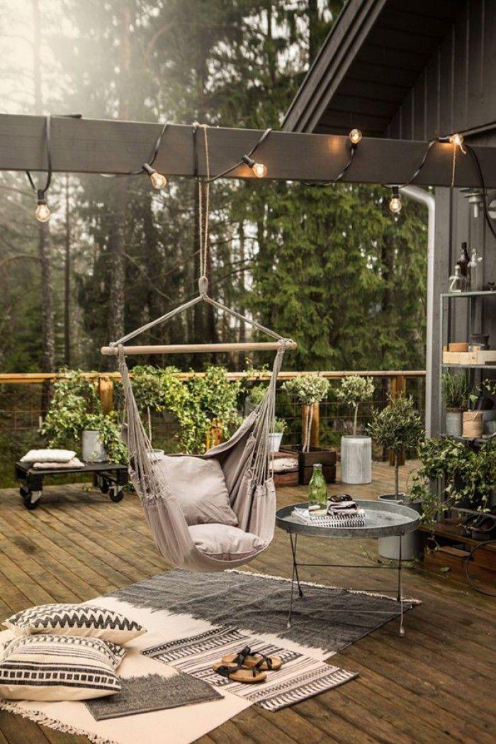 Een bijzonder tuin terras met veel groene planten en boompjes en een gezellig hoekje met stoffen hangstoel, tafeltje, kleed en kussens.
