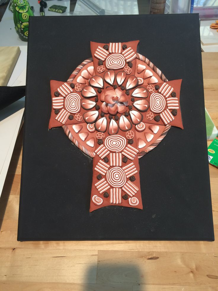 Terracotta and white polymer clay cross glued on black painted canvas with Tacky glue. By Pat Brown. See this design on printable art at https://fineartamerica.com/featured/clay-cross-01-pat-brown.html.