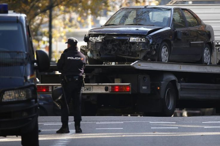 A police officer stands guard as a car that was driven into the headquarters of Spain's ruling People's Party (PP) is towed away in Madrid December 19, 2014. An unemployed Spaniard who said he was a ruined businessman rammed a car containing gas cylinders into the headquarters of Spain's ruling People's Party triggering a major police alert, official spokesmen said. REUTERS/Juan Medina