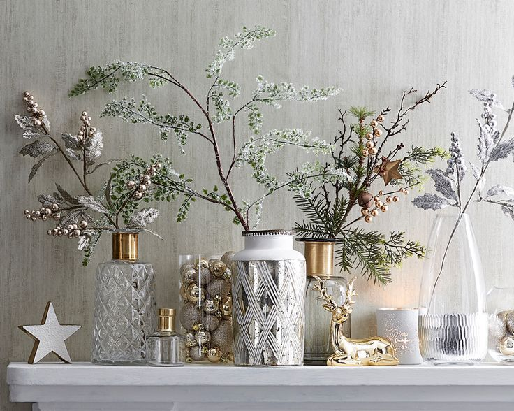 A great way to bring a touch of Christmas cheer to your home is to decorate a side table with a collection of Christmas sprays. Fill an assortment of vases with frosted evergreen stems and sparkling sprays and decorate them with your favourite ornaments. A couple of key Christmas decorative pieces bring the final touch of magic to the space. #christmas #christmasdecorating #bedbathntable