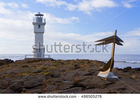 White Icelandic lighthouse with anchor in front of him, port of Akranes, Iceland