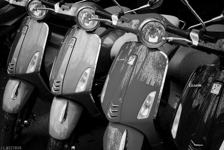 Row of Vespas for sale sitting in the rain