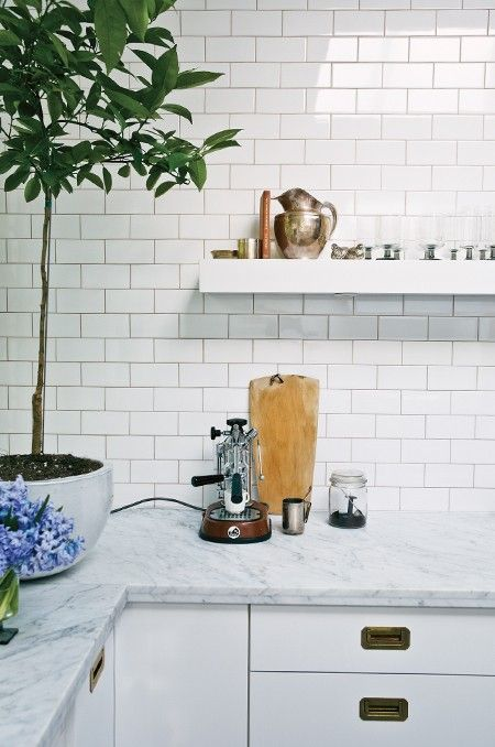 Sleek Subway Tiles - Ceiling-height subway tiles and open shelving create the feel of a European bistro kitchen, brass kickplates. Unlacquered brass hardware in vintage shops and on eBay.  Products:  Tiles, Antica Tile & Stone; marble counters, United Marble; cabinets, Ikea.