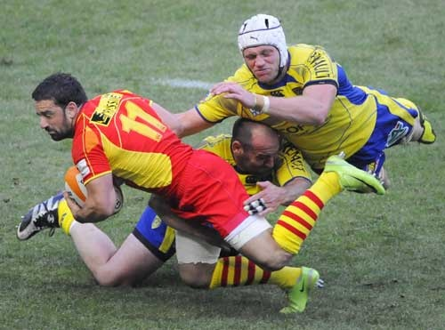 Perpignan wing Julien Candelon is tackled by the Clermont defence