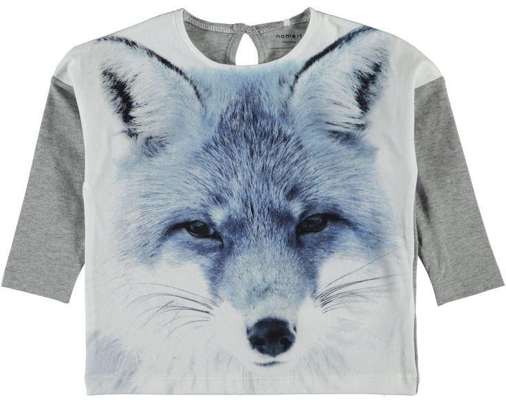 Meisjes tshirt NITFLIPPA van het merk Name-it. Dit is een licht grijze tshirt, voorzien van een ronde hals en lange mouwen. De shirt heeft een grote print van een wolven kop