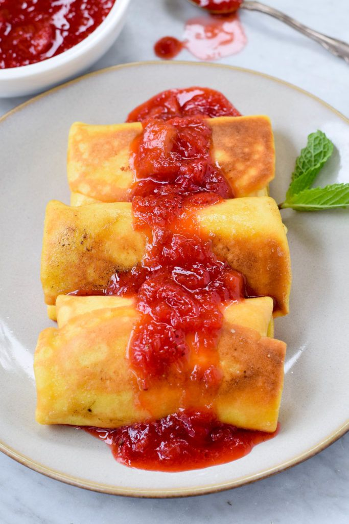 Homemade blintzes with cheese filling and strawberry-rhubarb compote. A special treat for breakfast or brunch. Make ahead!