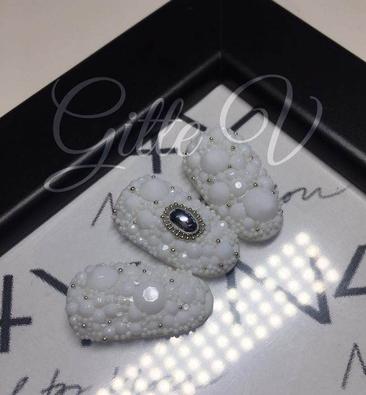 White nails here with white diamonds and white beads, nail art with silver stone and silver beads. Wedding nails
