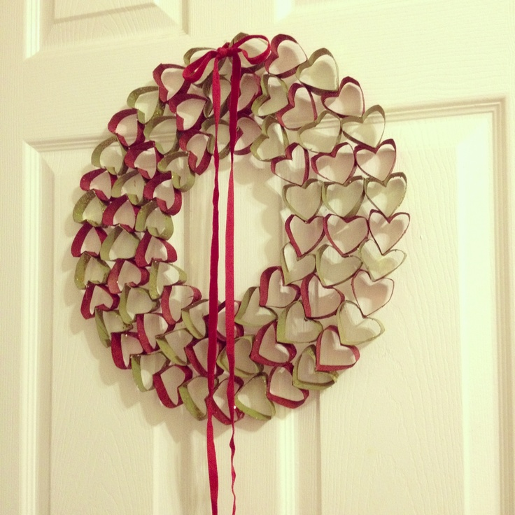 Finally made it myself! Wreath of Love    1) Collect roughly 4 paper towel rolls  2) Fold them then invert one side to make a pointy heart-shape  3) Cut up into individual hearts and round out the edges  4) Spray paint (in a cardboard box to avoid mess) & glitter  5) Start with smallest circle- use a hot glue gun to glue the hearts together  6) Add more layers as desired  7) Top off with a bow!