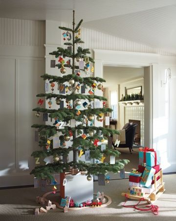 Darling Christmas tree for a playroom. Love the wooden train set around the tree! - Martha Stewart