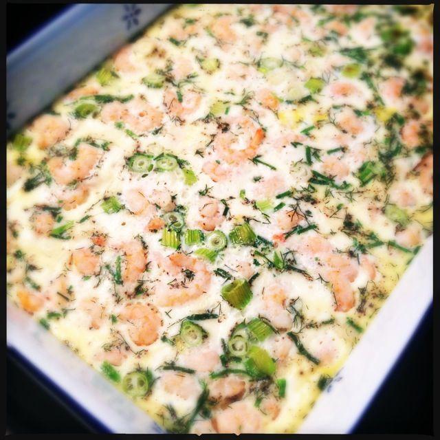 Ei uit de oven met garnalen en kruiden - 6 eieren - 100ml melk - 2 lente ui - 200gr garnalen - 2 takjes dille - 6 takjes bieslook - gemalen zwarte peper - zeezout