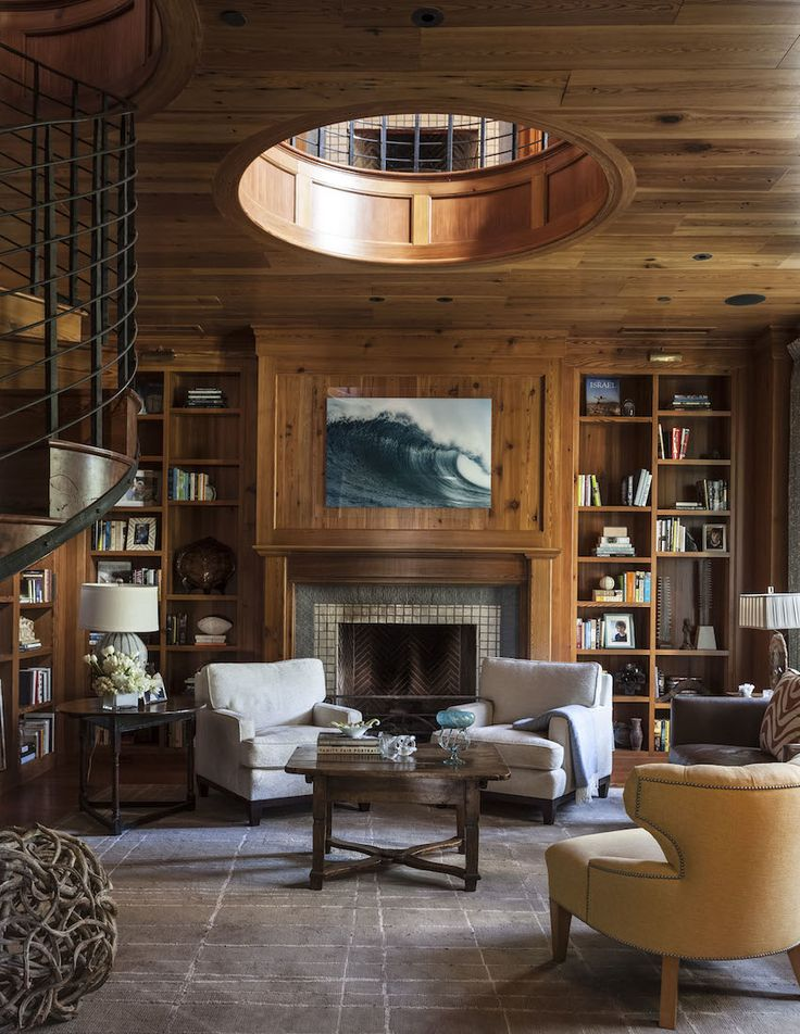 Amazing, rich study featuring wooden walls and ceilings with a spiral staircase leading upstairs, built-in bookshelves along the wall, carpeted floors, a fireplace and traditional furniture | Collins Interiors