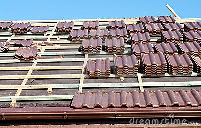 Installation of wide format brown ceramic roof tiles.