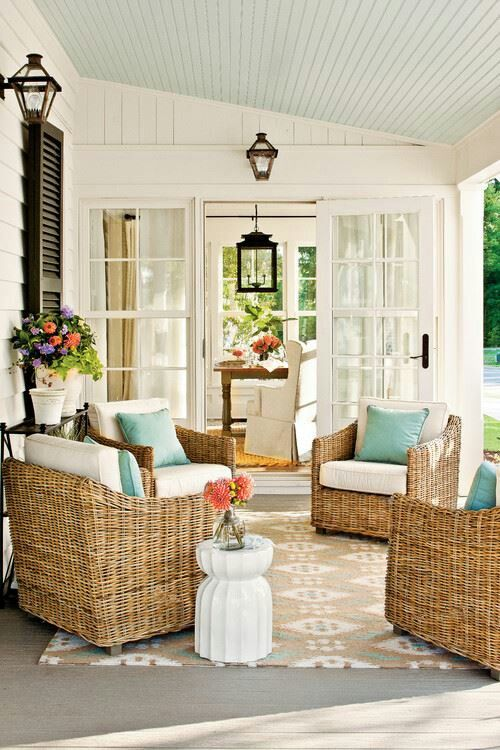 Coastal porch with light blue ceiling and wicker chairs