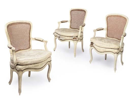 A SET OF THREE ROYAL LOUIS XV WHITE AND CREAM PAINTED CANED FAUTEUILS EN CABRIOLE POSSIBLY ITALIAN, CIRCA 1760-65  Each with a cartouche shaped back and scrolled padded arms above a white damask upholstered serpentine seat and squab cushion on cabriole legs with leaf-capped feet. FROM THE COLLECTION OF S.A.R. LA PRINCIPESSA REALE MARIA GABRIELLA DI SAVOIA.