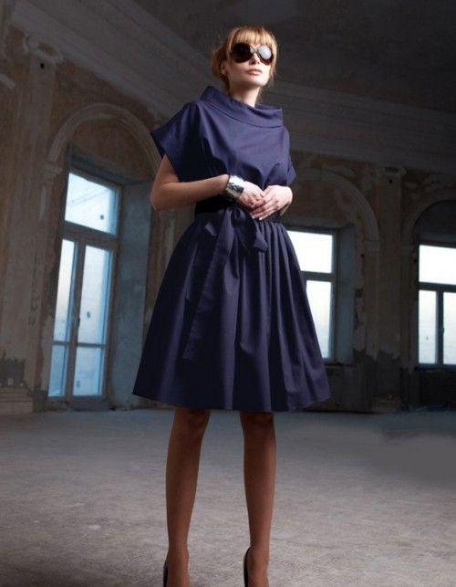 Powrót modelu Audrey, inspirowanym stylem Audrey Hepburn. Sukienka uszyta z włoskiej cienkiej tkaniny wełnianej, kolor grafit wpadający w granat. Sukienka o kroju kimonowym, z wysoką stójką i mankietami, marszczona w talii, z kieszeniami i szerokim pasem w komplecie. Długość ok. 98cm. Modelka ma 170 cm wzrostu i prezentuje rozmiar 36