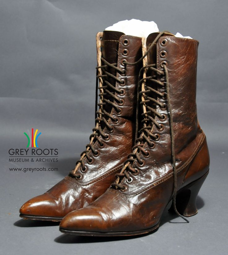 A pair of ladies', high-topped, button-up, brown leather boots. The boots have very pointed toes and a shaped, stacked heel. They are pictured here with their original brown laces. Grey Roots Museum & Archives Collection.