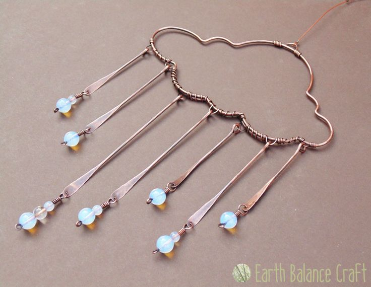 Rainy Days Suncatcher - A copper rain cloud hanging decoration with seven rain droplets made up of wire paddles and a glass beaded droplet.