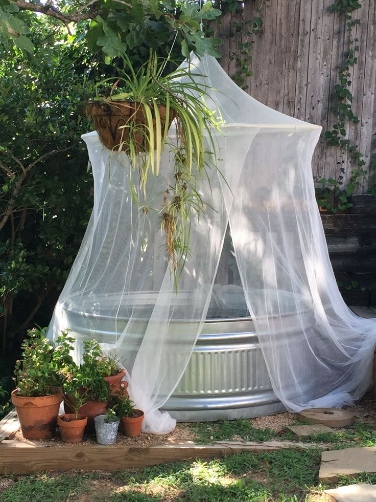 IKEA Mosquito net around a stock tank pool. There is a pump and drain to keep it clean through out the summer. #tractorsupply #IKEA #backyards #letsaddsprinklesblog