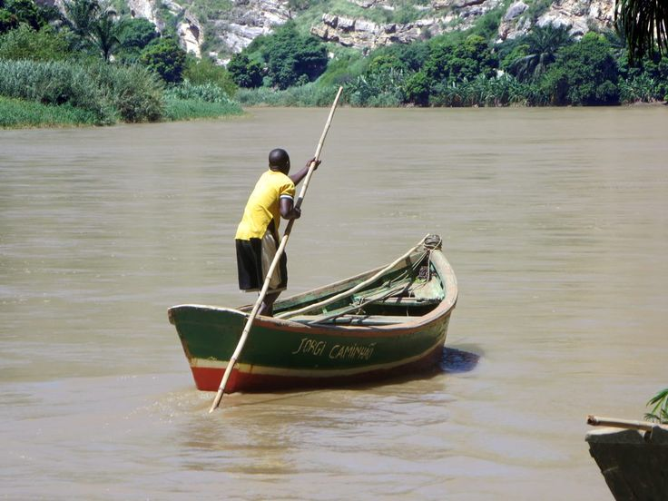 A man propels a small boat up the Catumbela River in western Angola.