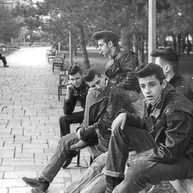 U.S. Greasers, 1950s. Greaser: a person who dresses in rockabilly fashion and styles his hair in a pompadour or other tall retro hairstyle with a petroleum based pomade, such as seen in the movies: The Outsiders, West Side Story, Rebel Without Cause, etc (from urban dictionary)