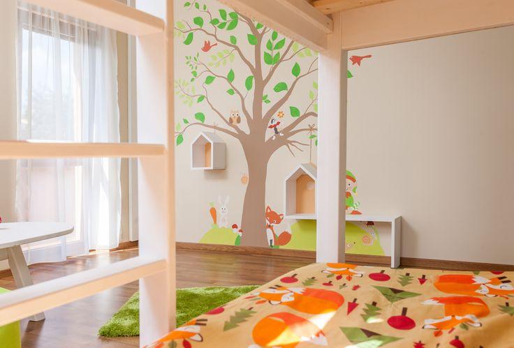 Nástěnná dekorace stromu s veselými zvířátky dominuje volné stěně