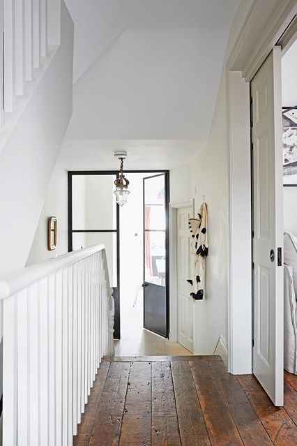 The black doors and the neutral palette used for the walls create a contemporary contrast with the reclaimed wood floor. On the right, pocket sliding doors open up to a seating area-cum-spare room while the stairs opposite lead down to the kitchen.