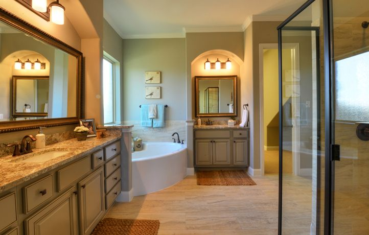 Luxrious Master Bath featuring cultured marble vanities and spacious garden tub in our Village Builders home in Dripping Springs