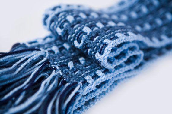 Цвет шарфа содержит в себе несколько оттенков джинсовой ткани. Структура шарфа представляет собой элементы плетеного полотна, частично связанного крючком. Размер: 18 см х 210см, бахрома ни в счет.