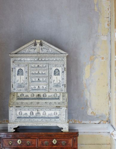 PROPERTY REMOVED FROM MS STATENDAM AND MS RYNDAM OF THE RENOWNED HOLLAND AMERICA LINE: An Anglo-Indian etched ivory and sandalwood table bureau cabinet, Vizagapatam, late 18th century.