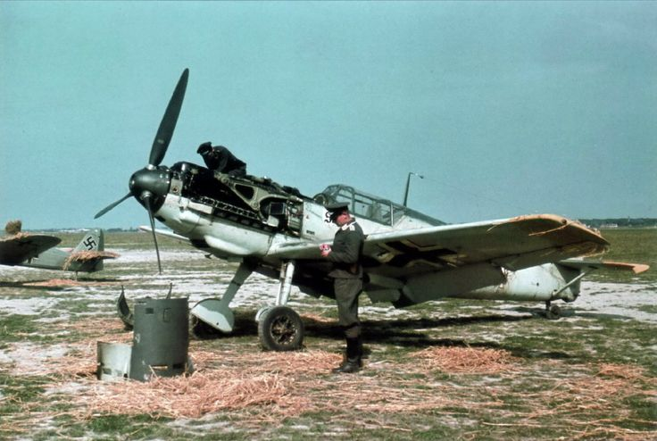 "Messerschmitt Bf 109 ""White 13"" with its engine cowling removed. A bullet hole is visible in the machine-gun cover sitting on the ground, indicating that the aircraft had been damaged in combat. A technician is examining the damage. Third Reich Color Pictures."