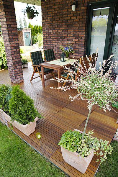 Krytá terasa obklopená květinami v létě nahrazuje obývací pokoj.