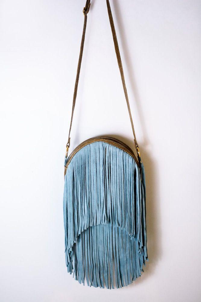 Bolso redondo en cuero marrón con textura, con flecos y detalles en cuero azul. Forro de algodón con bolsillo interior.Medidas 25x25cm.Hecho a mano.