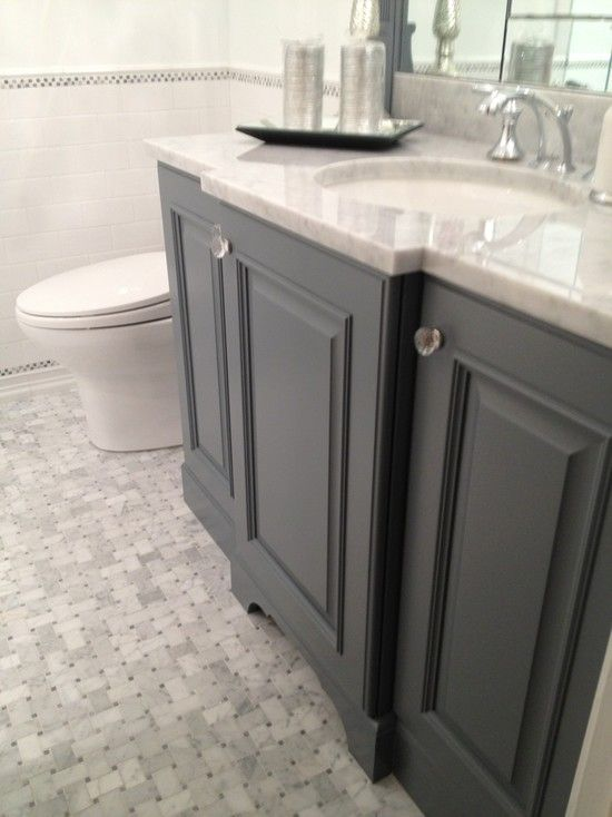 Stunning guest bath with gray bathroom vanity paired with carrara marble countertop and subway tile backsplash. Gray bathroom cabinets with crystal knobs and polished nickel faucet kit. Bathroom floor composed of marble basketweave tiles and subway tile baseboard.