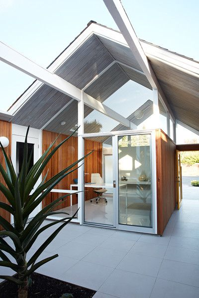 As one of Eichler's courtyard models, the home's office looks directly through the atrium and into the glass-enclosed living room, providing the ultimate indoor/outdoor feeling. The gray porcelain tile that Klopf Architecture installed in the interior is continued into the atrium.