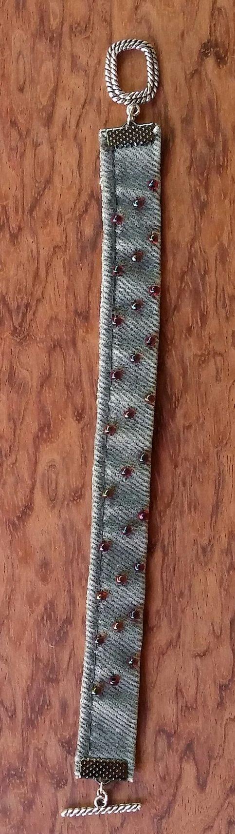 Esta pulsera denim gris se hace de un par de reciclado, pantalones de mezclilla gris reciclado. Hay granos de la semilla de cristal roja cosidos sobre el dril de algodón con un hilo de nylon resistente. Estos granos de la semilla de cristal rojo son translúcidos y en el sol reluce de azul y púrpura. Son un gran toque de denim! Las conexiones y cierre de palanca son de metal plateado plata.  Esta pulsera gris del dril de algodón es muy cómoda. No pellizcar o lastimar su brazo cuando se sitúa…