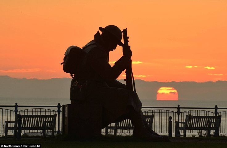 The sun rises in Seaham, County Durham, above the statue of 'Tommy' depicting a solider s...