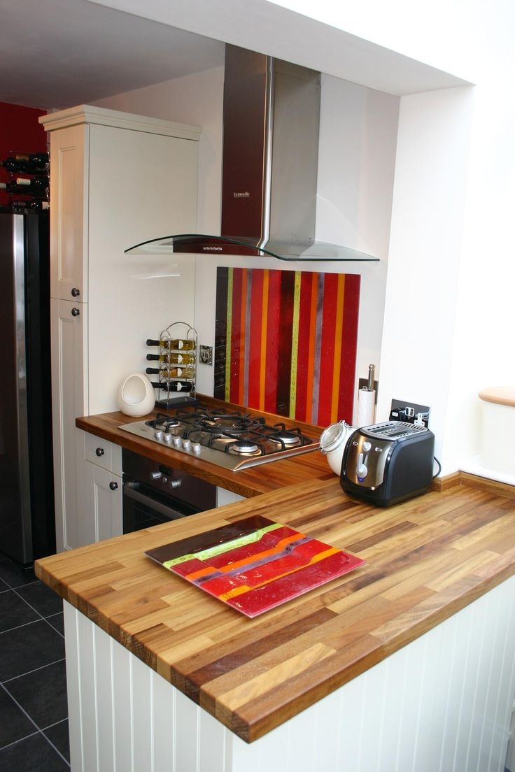 This Salsa fused glass splashback has a unique mixture of warm colourful stripes running vertically.  As you can see it tones nicely with the warmth of the modern worktops. It makes a real statement in this minimalist modern white kitchen.