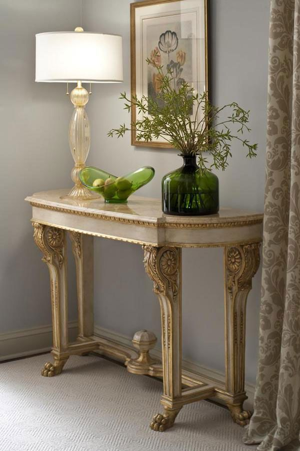 room setting with clear and gold venetian glass lamp hand blown on the island of murano italy and empire style carved wood console table with marble top