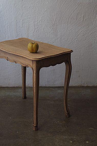 ティーサイドテーブル-antique oak side table 緩やかな天板のカッティングやなだらかなS字カブリオレレッグをもう少し「近しい」雰囲気にしたく、ステイン塗装を剥がしプレーンなオークの地色を。幕板下や天板縁のモールディング装飾が影に変化を付けて程良いアクセントに。塗膜無く無垢のままの天板ですので、濡れたコップ等直に置かれますと滲みの原因となります。少し色目は濃くなりますがクリアワックスを適宜塗布する事で滲み予防になります。
