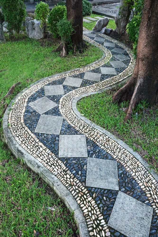 A Curving Pathway With Diamond Pavers Filled With Blue And White Stones Is Making Its Way Through The Trees And Is C Walkways Paths Garden Pathway Garden Paths
