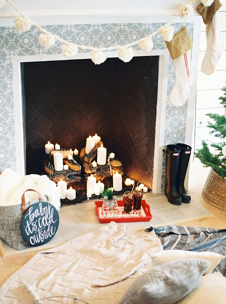 """pom pom garland with neutral stockings and """"baby its cold outside"""" sign by the fireplace with blankets // cute holiday styling"""